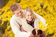 Bladeren van de het paarholding van de herfst de gelukkige in park Stock Foto's