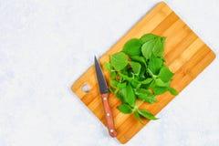 Bladeren van verse groene netel op een scherpe houten raad met een mes op een grijze concrete lijst Hoogste mening royalty-vrije stock afbeeldingen