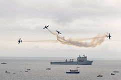 The blades bomb burst over ship. The blades display team flying extra300s with smoke in air display ove ships moored in bournemouth bay sept 1st 2012 stock images
