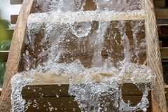 The blades of mill wheel rotates under a stream of water,. Close up view, open air museum stock photography