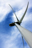 Blades of a Wind Turbine against Blue Sky. Wind Energy Generator in Spanish Field. Detail of Blades of turbine spinning many metres above the ground stock photo