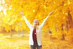 Bladnedgång, ung kvinna för lyckligt uttryck som har gyckel i varm solig höst royaltyfri foto