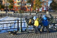 Blagoveshchensk, Россия, 21-ое октября 2017 2 малых дет рассматривают памятник к невозмутимому коту на embank Стоковые Фото