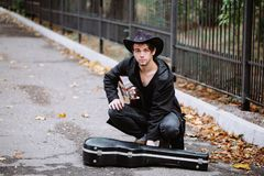 Blak guitar case. Young man with black guitar case in the park stock image