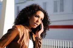 Blak woman talking on phone. Portrait of pretty blak woman in urban background talking on phone Royalty Free Stock Image