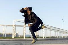 Ο μοντέρνος νέος αρσενικός χορευτής στα μοντέρνα μαύρα ενδύματα που χορεύουν blake χορεύει σε μια οδό στην πόλη σε ένα απόγευμα φ στοκ εικόνες