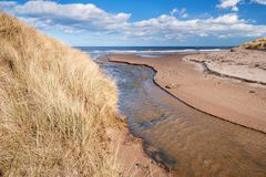 Blakemoor Burn crosses Druridge Beach. Druridge Bay is a seven mile long beach in Northumberland between Amble to the north and Cresswell to the south Royalty Free Stock Photos