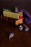 Blaks figs and green books on wooden table Royalty Free Stock Photography