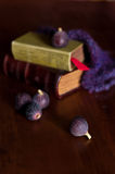 Blaks figs and green books on wooden table Royalty Free Stock Images