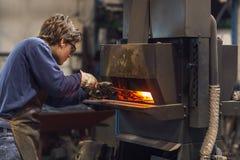 Blaksmith novo que trabalha em uma oficina metalúrgica foto de stock royalty free