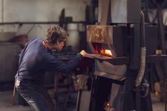 Blaksmith novo que trabalha em uma oficina metalúrgica imagem de stock
