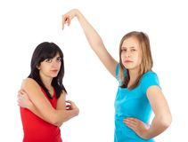 The blame lies with her!. Blond girl blaming her brunette friend Royalty Free Stock Image