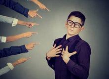 blaming Bezorgde die mens in ontkenning door mensen wordt beoordeeld die vingers op hem richten Stock Fotografie