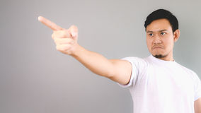 He is blaming or firing someone. An asian man with white t-shirt and grey background stock image