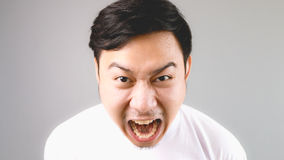 Blaming out loud at the camera. An asian man with white t-shirt and grey background stock photos