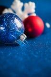 Blanc, argent et ornements rouges de Noël sur le fond bleu-foncé de scintillement avec l'espace pour le texte Photos stock