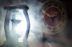blanc au moment de l'exécution d'isolement par concept de fond Silhouette d'horloge de sablier et d'horloge en bois de vieux vint Photos stock