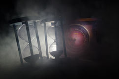 blanc au moment de l'exécution d'isolement par concept de fond Silhouette d'horloge et de fumée de sablier sur le fond foncé avec Photographie stock libre de droits