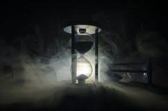 blanc au moment de l'exécution d'isolement par concept de fond Silhouette d'horloge et de fumée de sablier sur le fond foncé avec Photo stock