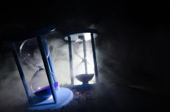 blanc au moment de l'exécution d'isolement par concept de fond Silhouette d'horloge et de fumée de sablier sur le fond foncé avec Image libre de droits