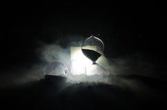 blanc au moment de l'exécution d'isolement par concept de fond Silhouette d'horloge et de fumée de sablier sur le fond foncé avec Photos libres de droits