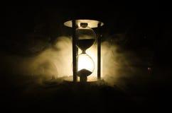 blanc au moment de l'exécution d'isolement par concept de fond Silhouette d'horloge et de fumée de sablier sur le fond foncé avec Photographie stock