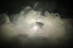 blanc au moment de l'exécution d'isolement par concept de fond Silhouette d'horloge et de fumée de sablier sur le fond foncé avec Image stock