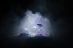 blanc au moment de l'exécution d'isolement par concept de fond Silhouette d'horloge et de fumée de sablier sur le fond foncé avec Photos stock