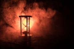 blanc au moment de l'exécution d'isolement par concept de fond La silhouette de l'horloge de sablier et la fumée sur le fond fonc Image stock