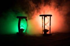 blanc au moment de l'exécution d'isolement par concept de fond La silhouette de l'horloge de sablier et la fumée sur le fond fonc Photographie stock