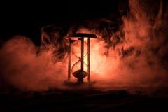blanc au moment de l'exécution d'isolement par concept de fond La silhouette de l'horloge de sablier et la fumée sur le fond fonc Images stock