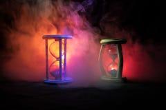 blanc au moment de l'exécution d'isolement par concept de fond La silhouette de l'horloge de sablier et la fumée sur le fond fonc Photographie stock libre de droits
