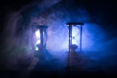 blanc au moment de l'exécution d'isolement par concept de fond La silhouette de l'horloge de sablier et la fumée sur le fond fonc Photo stock