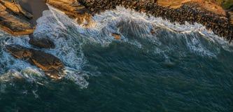 Blanc avec la mousse--Littoral rocailleux au coucher du soleil, San Diego Photo libre de droits