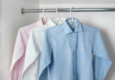 Blanc, bleu et rose nettoyez les chemises des hommes repassés accrochant sur le cintre Images libres de droits