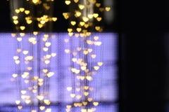 Blanc coloré accrochant en forme de coeur de bokeh d'éclairage de fond de valentine d'or jaune pour le papier peint de contexte d Photo stock