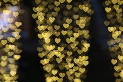 Blanc coloré accrochant en forme de coeur de bokeh d'éclairage de fond de valentine d'or jaune pour le papier peint de contexte d Photographie stock