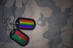 blanc d'armée, étiquette de chien avec le drapeau de Burkina Faso et le drapeau gai d'arc-en-ciel sur le fond kaki de texture Images libres de droits