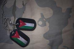 Blanc d'armée, étiquette de chien avec le drapeau de la Jordanie sur le fond kaki de texture Photos libres de droits