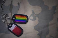 blanc d'armée, étiquette de chien avec le drapeau du Bahrain et le drapeau gai d'arc-en-ciel sur le fond kaki de texture Photographie stock