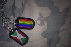 blanc d'armée, étiquette de chien avec le drapeau du Burundi et le drapeau gai d'arc-en-ciel sur le fond kaki de texture Photos stock