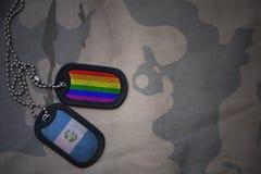 blanc d'armée, étiquette de chien avec le drapeau du Guatemala et le drapeau gai d'arc-en-ciel sur le fond kaki de texture Photo libre de droits