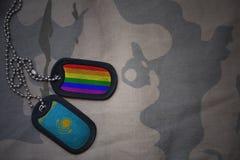 blanc d'armée, étiquette de chien avec le drapeau du Kazakhstan et le drapeau gai d'arc-en-ciel sur le fond kaki de texture Images stock