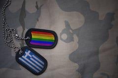 blanc d'armée, étiquette de chien avec le drapeau de la Grèce et le drapeau gai d'arc-en-ciel sur le fond kaki de texture Photo libre de droits