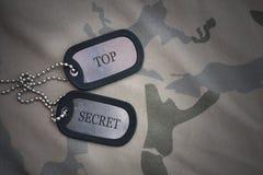 Blanc d'armée, étiquette de chien avec le top secret des textes sur le fond kaki de texture Photo stock
