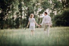 blanc d'isolement de vue arrière jeunes couples heureux marchant sur la pelouse en parc image stock