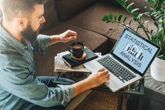 blanc d'isolement de vue arrière L'homme, entrepreneur, s'assied à la maison, travaillant à l'ordinateur portable avec l'analyse  image libre de droits