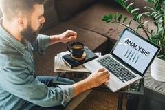blanc d'isolement de vue arrière L'homme, entrepreneur, s'assied à la maison, travaillant à l'ordinateur portable avec l'analyse  photo libre de droits