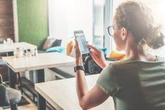 blanc d'isolement de vue arrière La fille de hippie s'assied en café à la table, utilisant le smartphone et regarde sur son écran Photographie stock libre de droits