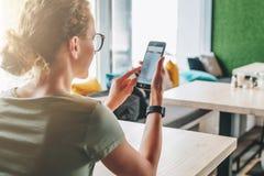 blanc d'isolement de vue arrière La fille de hippie s'assied en café à la table, utilisant le smartphone et regarde sur son écran Photographie stock